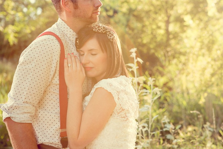 A bride wearing a leapord print hair tie and 60s style dress rests her head on groom chest who is wearing a spotty shirt and red braces
