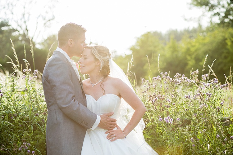 A romantic photograph of groom kissing bride on the head with whimsical sunshine amongst wild flowers.