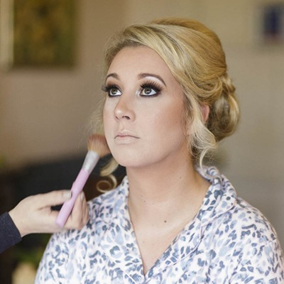 A blonde bride at Berwick Lodge sits having her make-up applied