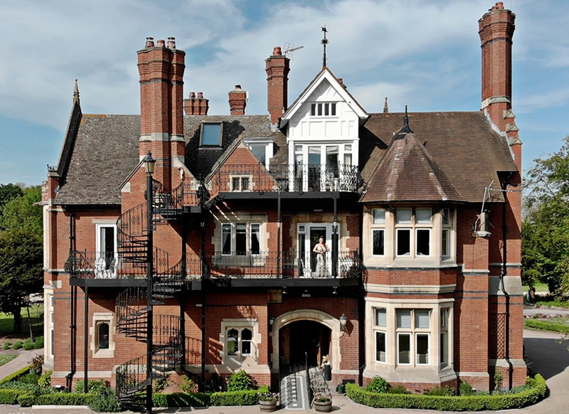 A wide aerial image of Berwick Lodge manor house in red brick with a bride on the balcony
