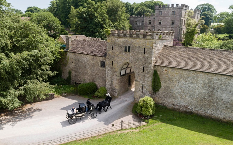 An aerial photograph showing a horse drawn carriage at Clearwell Castle gates.