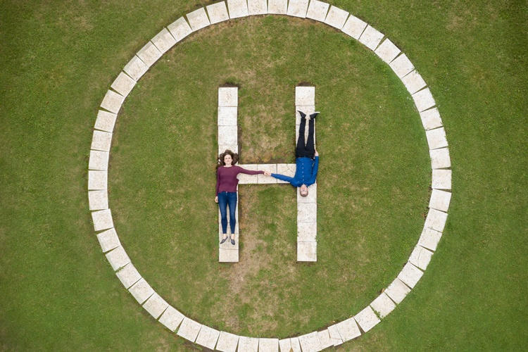 A top down aerial image of a couple laying down on a helicopter pad