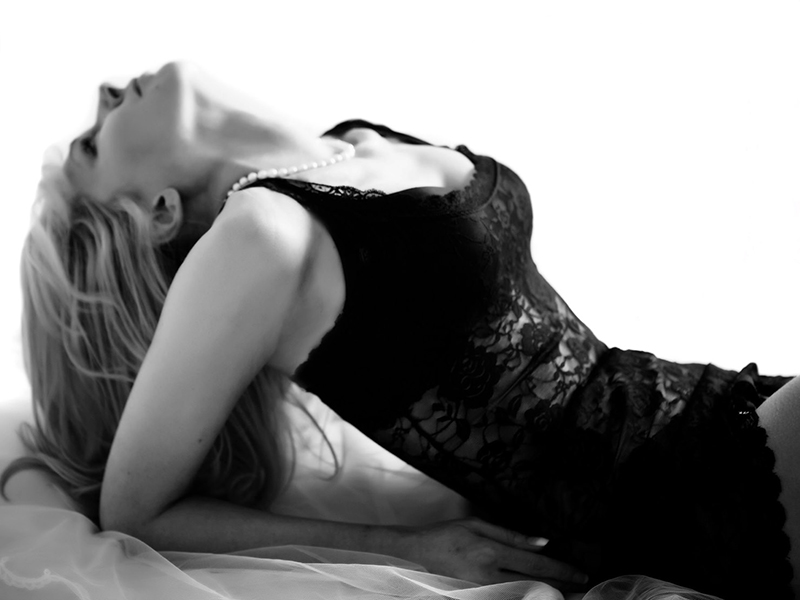 Black and white photograph a of a woman resting on her elbows tipping her head back, wearing a black lace bodice, against a white background, cropped from her thighs up.