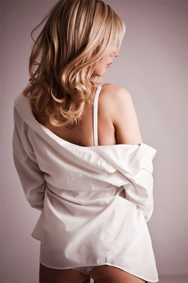 A blonde lady with her back to the camera wearing a mans white shirt that is falling off her shoulder to reveal her underwear.