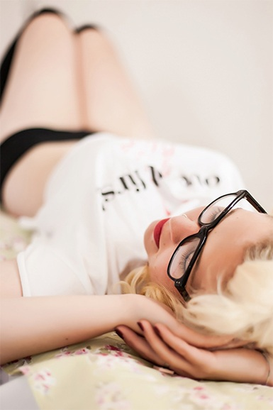 Shot from the head down in a shallow depth of field the images show a blonde girl wearing glasses and a short t-shirt with black hold up tights in the distance.