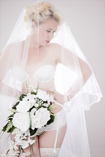 Photograph of bride wearing just her underwear and wedding veil holds a white bouquet which covers her white stockings and suspender belt