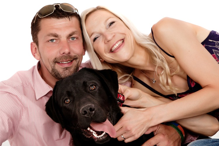 A couple and a black Labrador are photographed from the waist up for a portrait of the family