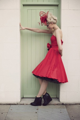 a full length photograph a a lady wearing a red dress