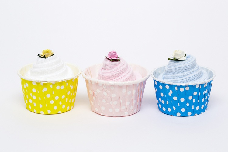 Three baby shower gifts in cupcake shapes photographed in the studio