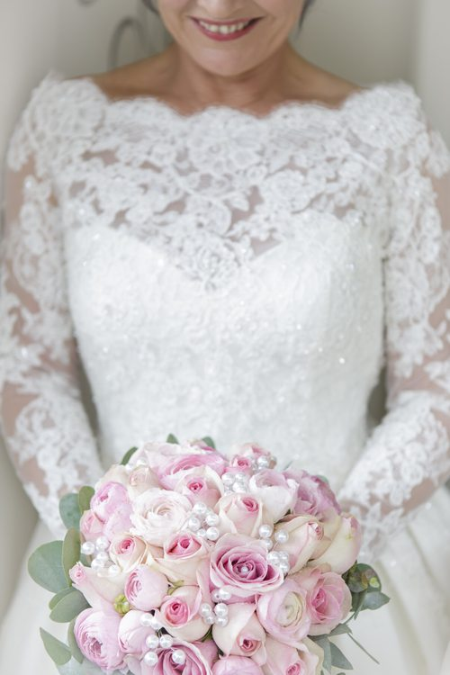 A cropped images of a bride holding a pink bouquet