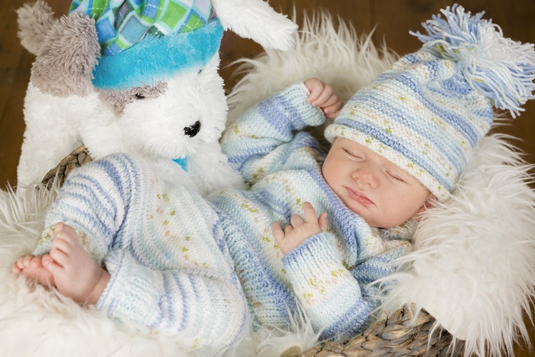 A baby asleep wearing a blue knitted outfit