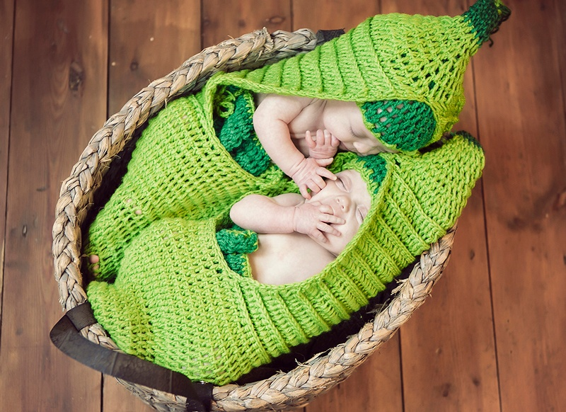 Two babies sleeping in a basket on a wooden floor dressed as peas