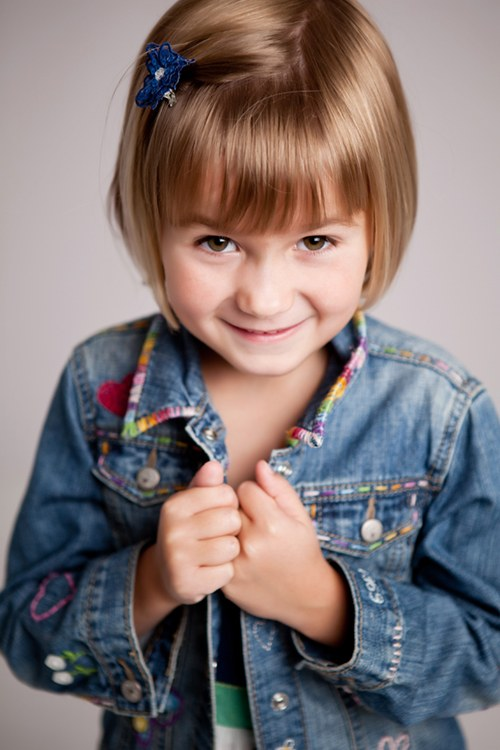 A waist up photo of a little girl wearing a denim jacket