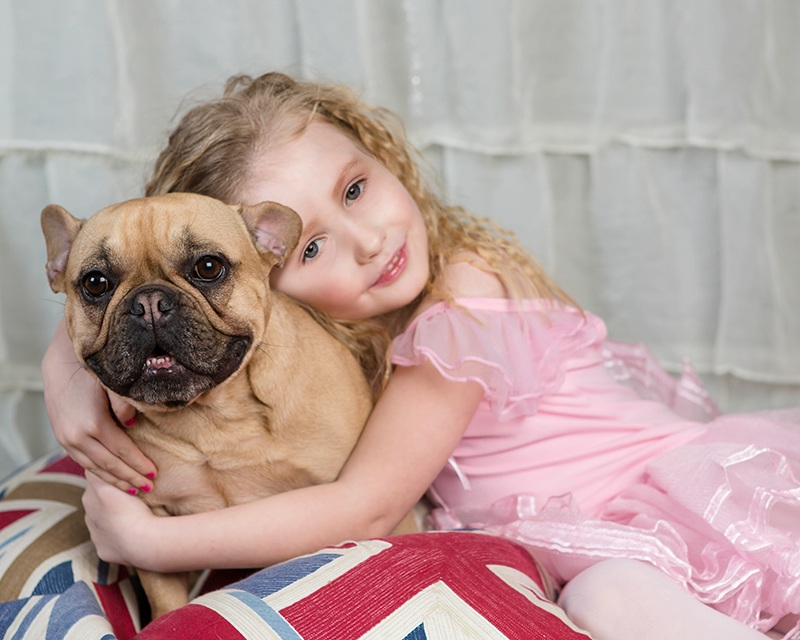 A little girl wearing pink hugging her dog