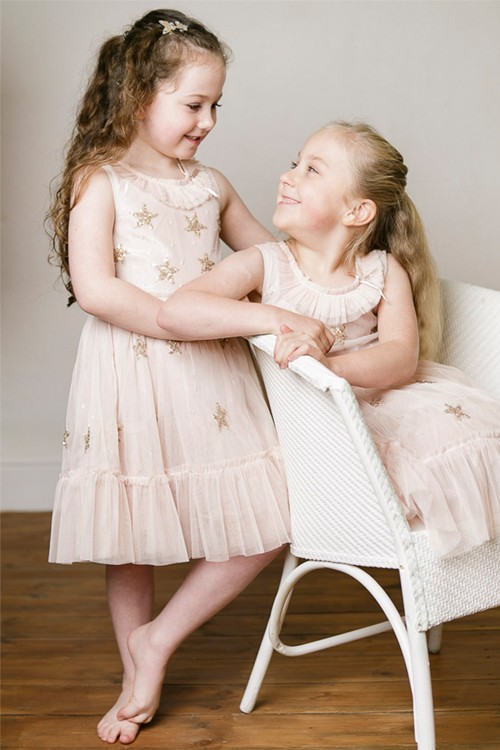 Two girls looking at each other and one is sitting on a white chair