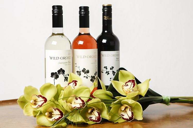 A commercial imange of 3 wine bottle with orchids in front