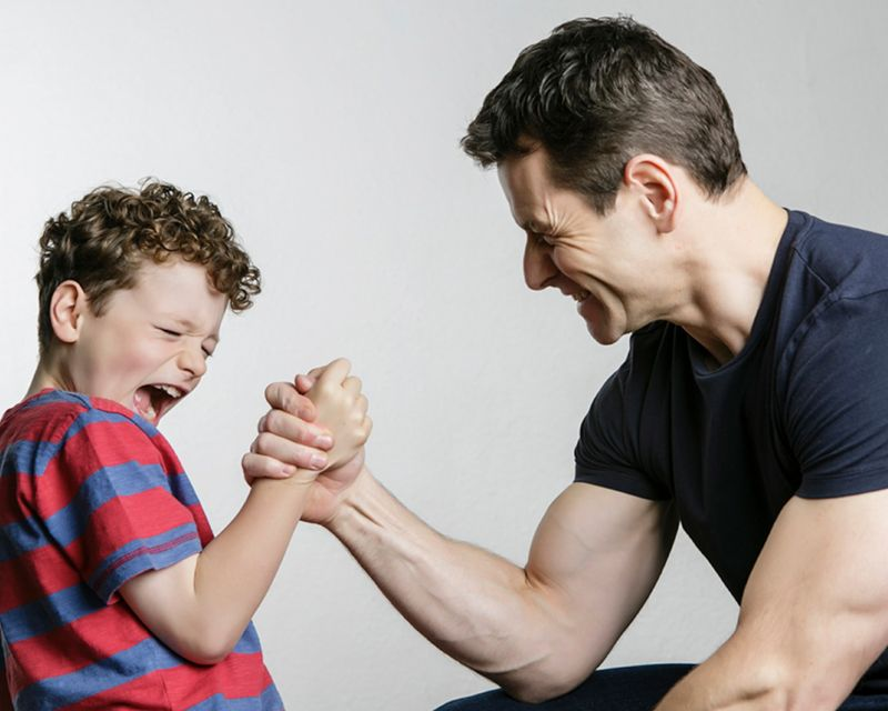 Action photo of father and son arm wrestling against a light grey background in the studio.