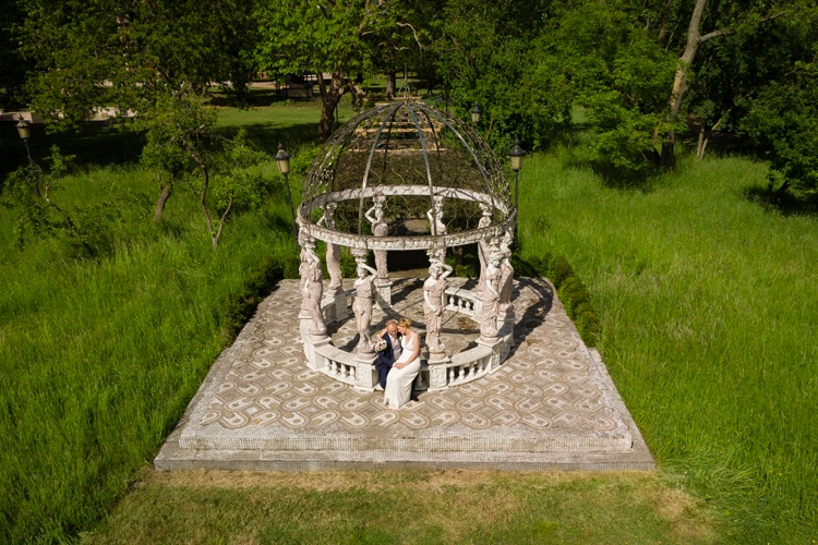 A wedding couple sitting in a stone and iron garden structure, image taken from the air.