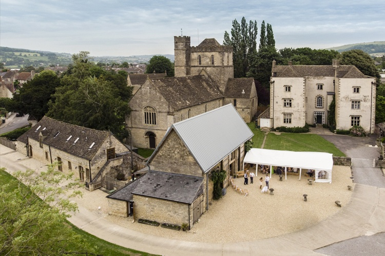 An aerial overview of a wedding venue including church and barn.