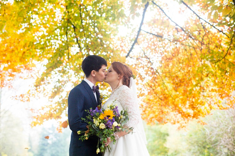 A wedding photograph taken of a Bride and groom kissing in autumn leaves