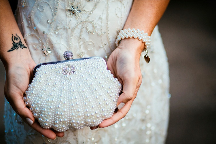 A wedding Photograph of a pearl clutch bag in brides hands