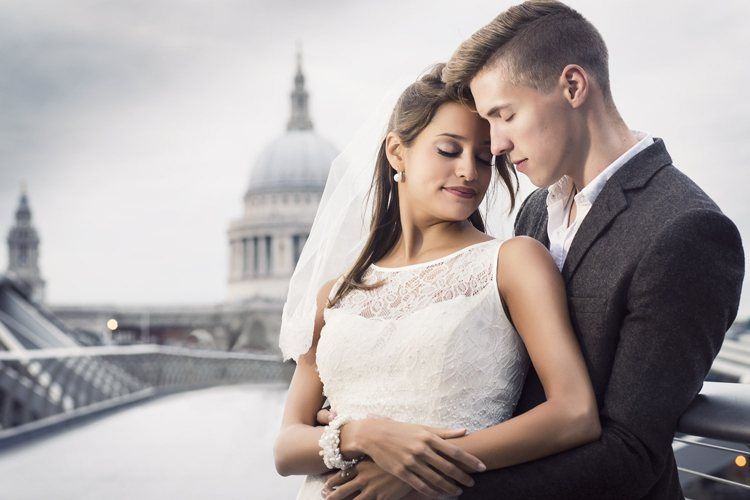 A wedding couple huggin on a bridge infront of St Paul cathedral in London